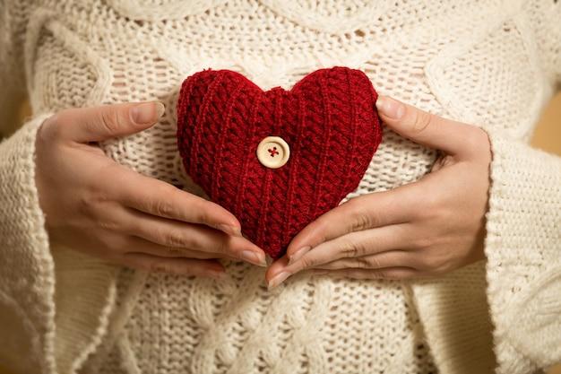 Mulher jovem posando com um coração vermelho em um suéter branco