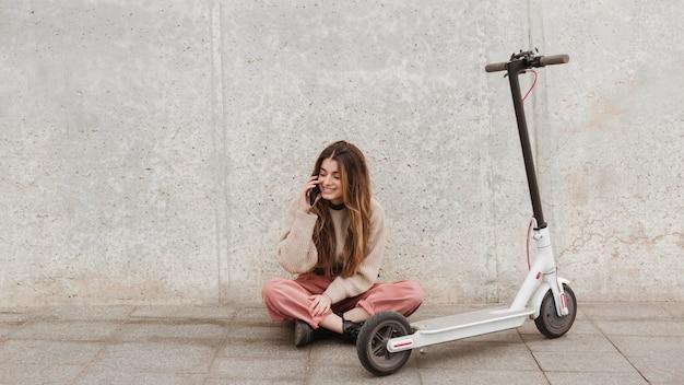 Mulher jovem posando com uma scooter elétrica