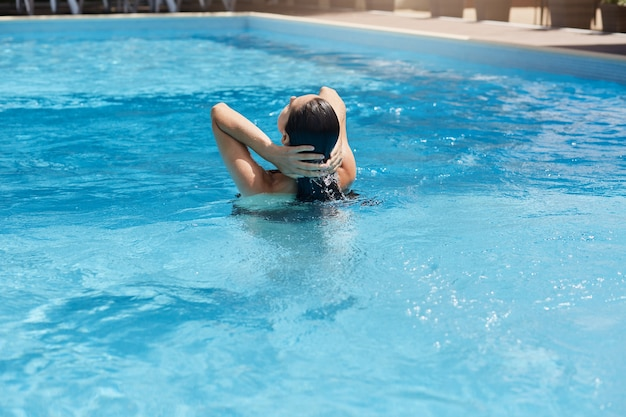 Mulher jovem posando de costas em pé na água azul e tocando seu cabelo escuro e molhado