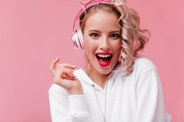 Mulher jovem posando e ouvindo música com seus fones de ouvido cor de rosa