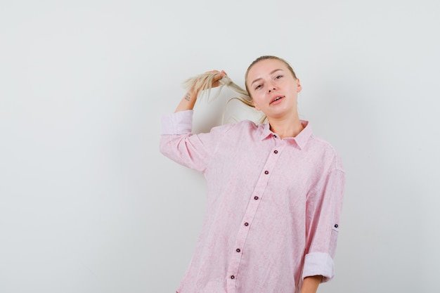 Mulher jovem posando enquanto segura uma mecha de camisa rosa e está bonita