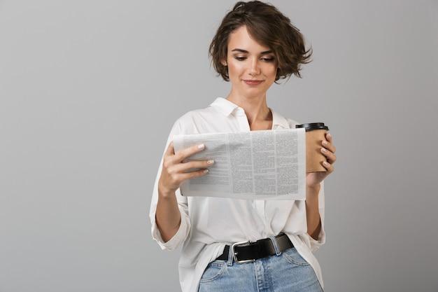 Mulher jovem posando isolada sobre uma parede cinza, bebendo café e segurando um jornal