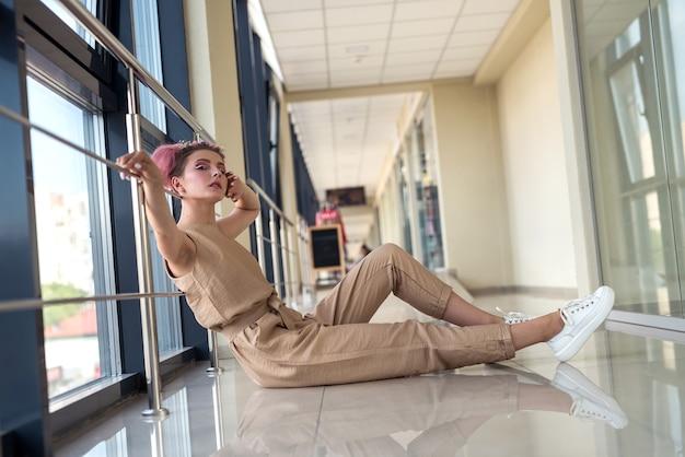 Mulher jovem posando para a câmera, sentada no chão no corredor