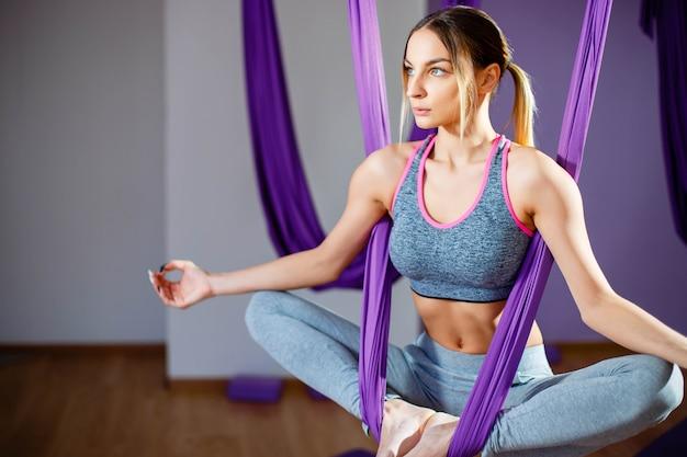 Mulher jovem, posar, fazendo, aéreo, ioga, exercício, com, rede