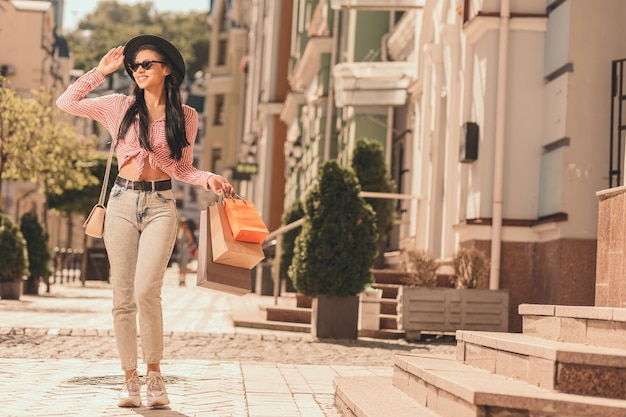 Mulher jovem positiva andando com sacos de papel na rua. banner do site