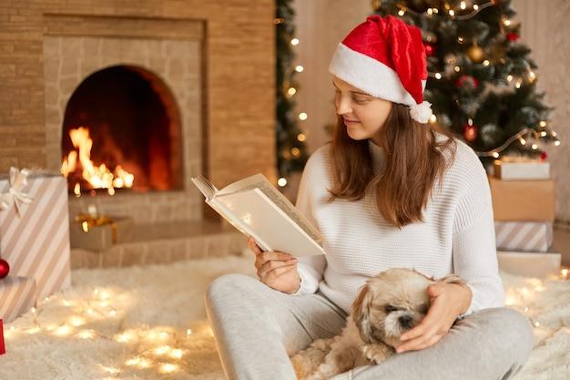 Mulher jovem positiva, aproveitando para passar o tempo com seu cachorro, adorável fêmea posando na festiva sala de estar com seu animal de estimação, lendo um livro enquanto se senta perto da árvore de natal e lareira.