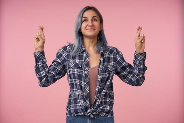 Mulher jovem positiva com cabelo curto azul cruzando os dedos para dar boa sorte enquanto faz um desejo e sorri gentilmente, em pé na rosa