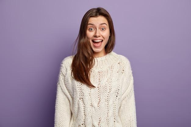 Mulher jovem positiva com expressão de alegria, abre a boca de surpresa, reage a notícias positivas inesperadas, usa um macacão branco, fica de pé contra a parede violeta, intrigada por dizer algo