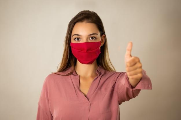 Mulher jovem positiva com máscara vermelha com baque no estúdio