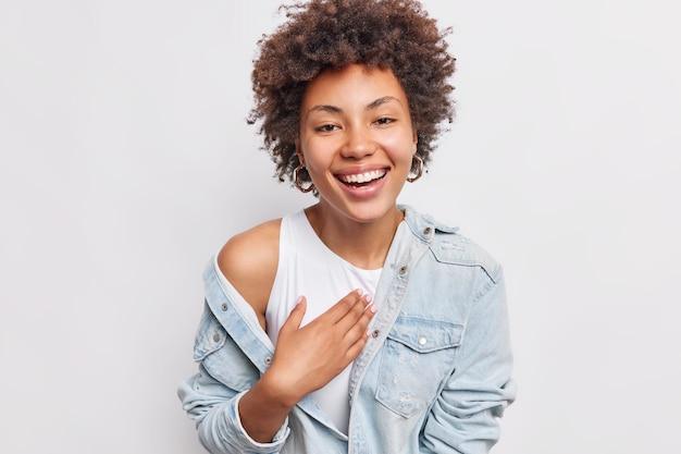 Mulher jovem positiva com sorrisos naturais de cabelo encaracolado expressa amplamente emoções sinceras, vestida com uma camisa jeans isolada sobre uma parede branca