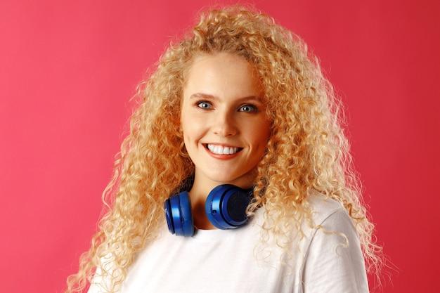 Mulher jovem positiva em pé com fones de ouvido azuis isolados