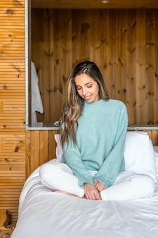 Mulher jovem positiva em roupa casual, sentada na cama, passando a manhã em um quarto aconchegante