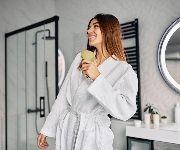 Mulher jovem positiva em um roupão de banho