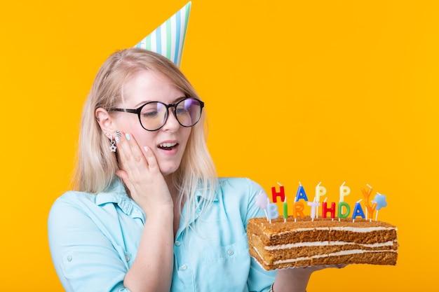 Mulher jovem positiva engraçada tem nas mãos um bolo caseiro com o feliz aniversário de inscrição posando em uma parede amarela. conceito de férias e aniversários.