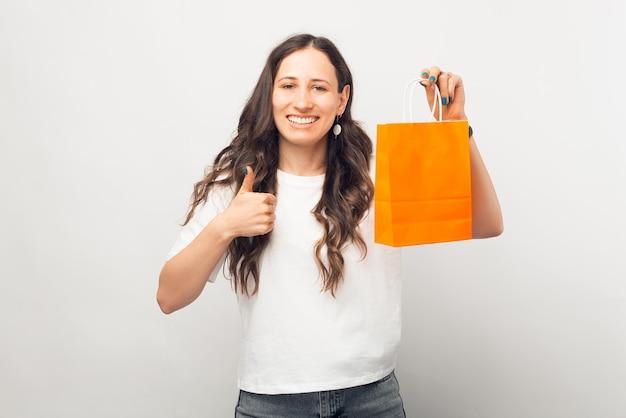 Mulher jovem positiva está se mostrando como um gesto e uma sacola de compras.