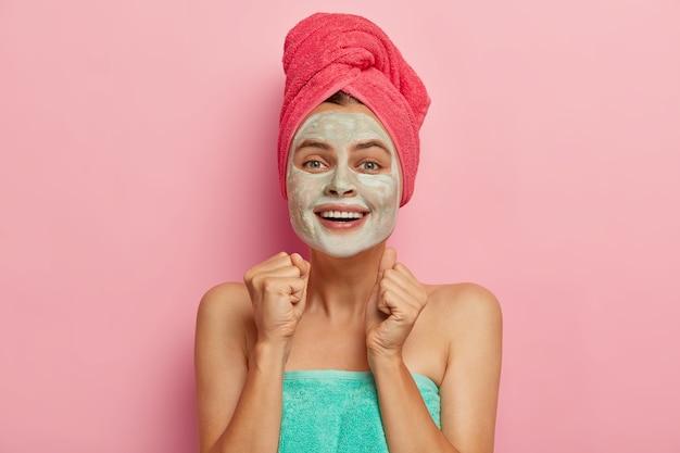 Mulher jovem positiva fecha os punhos de alegria, aplica máscara de argila no rosto, usa toalha rosa na cabeça, quer ter beleza natural, modela-se em ambientes internos, sorri amplamente, expressa felicidade bem estar