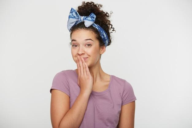 Mulher jovem positiva fechou a boca com a mão e parece brincalhão