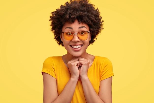 Mulher jovem positiva mantém as mãos juntas sob o queixo, tem um sorriso largo, dentes brancos perfeitos, vestida com uma camiseta brilhante