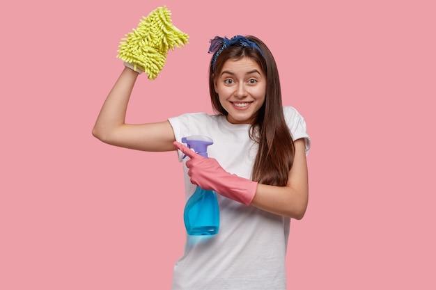 Mulher jovem positiva mostra músculos após um trabalho cansativo na casa, vestida com uma camiseta branca casual, segura um frasco de spray