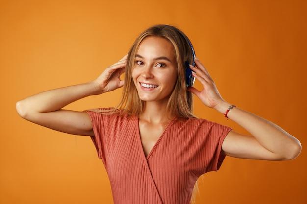 Mulher jovem positiva ouvindo música com fones de ouvido azuis close-up