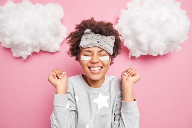 Mulher jovem positiva se alegra com boas notícias sorri amplamente mantém os olhos fechados aperta as mãos nos punhos usa pijama e máscara de dormir isolada sobre a parede rosa