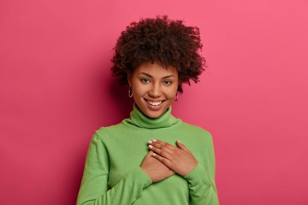 Mulher jovem positiva se sente grata, mantém as mãos pressionadas ao coração, usa uma blusa de gola alta verde, sorri positivamente, parece com um sorriso terno, isolada sobre uma parede rosa brilhante. muito obrigado