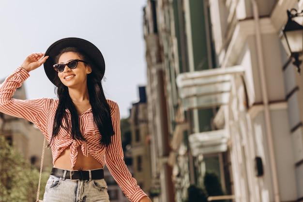 Mulher jovem positiva tocando seu chapéu em dia ensolarado. banner modelo