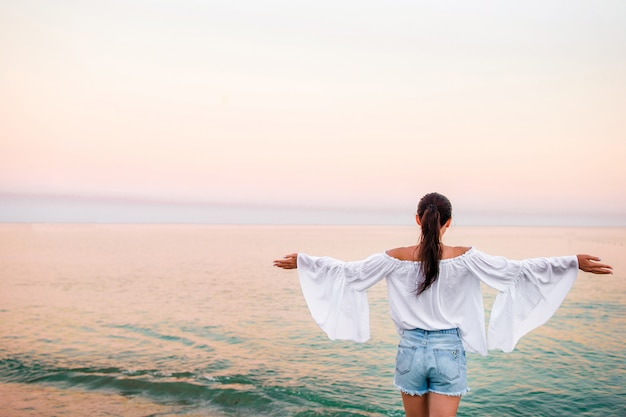 Mulher jovem, praia, em, pôr do sol