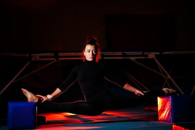 Mulher jovem pratica barbante sentado. atlética garota fazendo ginástica no ginásio. estilo de vida ativo