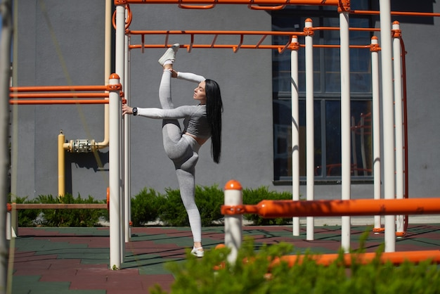 Mulher jovem pratica esportes em um playground moderno, com uma ampla extensão de pernas na posição vertical.
