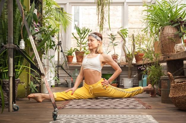Mulher jovem pratica ioga em casa entre flores.