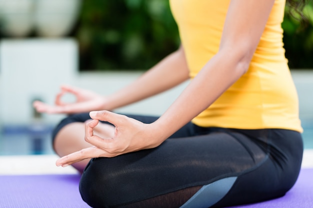 Mulher jovem, prática, ioga, em, posição lotus, ao ar livre
