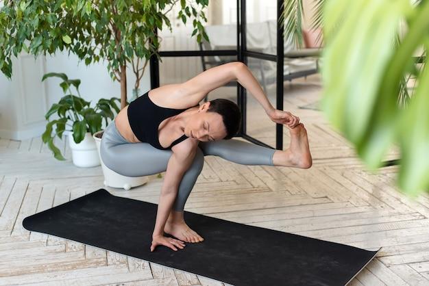 Mulher jovem pratica ioga em uma sala com plantas.