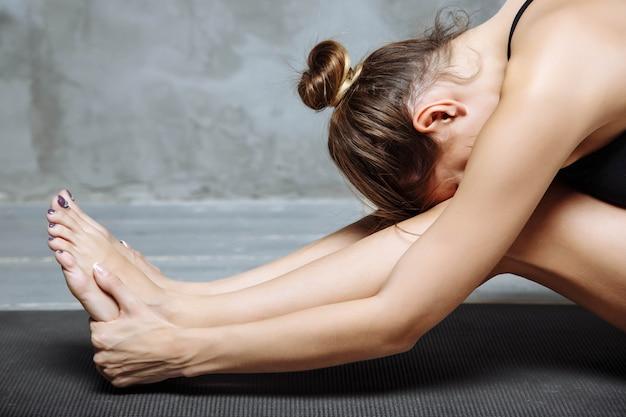 Mulher jovem, prática, ioga, sentando, em, sentada, curvatura dianteira, exercício