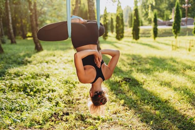 Mulher jovem, prática, voar, ioga, em, a, cabeça árvore, baixo