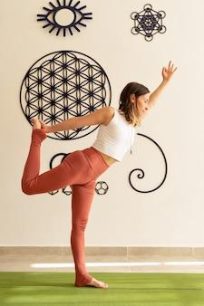 Mulher jovem praticando asanas de ioga com roupas esportivas