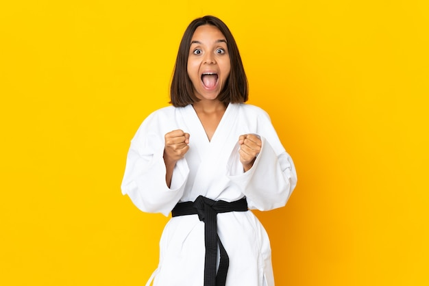 Mulher jovem praticando caratê isolada em fundo amarelo e comemorando a vitória na posição de vencedora