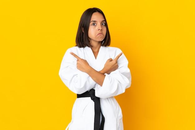 Mulher jovem praticando caratê isolada em uma parede amarela apontando para as laterais com dúvidas