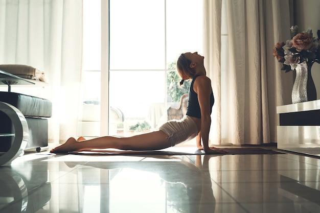 Mulher jovem praticando ioga dentro de casa. linda garota meditando e fazendo poses de ioga em casa