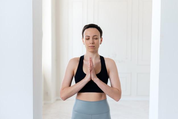 Mulher jovem praticando ioga e orando em um fundo interior de uma casa branca e minimalista