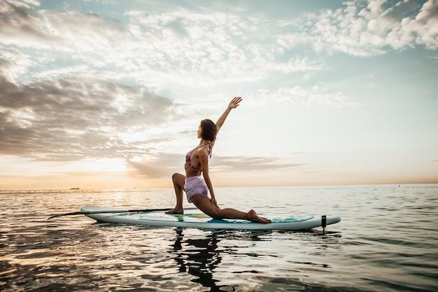 Mulher jovem praticando ioga em uma prancha de sup no lago ao nascer do sol