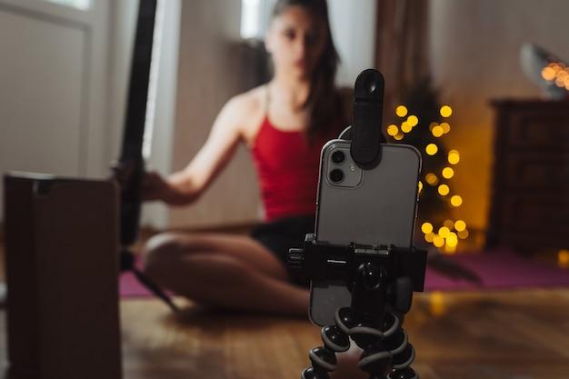 Mulher jovem praticando ioga está envolvida com o professor on-line