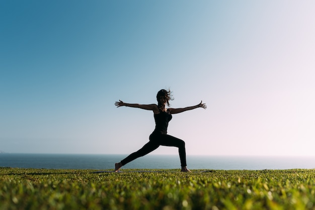 Mulher jovem praticando ioga na grama ao ar livre, abrindo os braços e despenteada