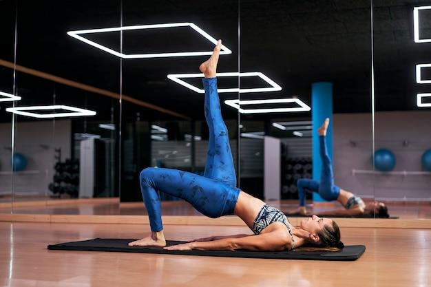 Mulher jovem praticando ioga ou pilates em uma academia, malhando com roupas esportivas azuis, fazendo exercícios de ponte de cotovelo