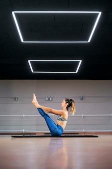 Mulher jovem praticando ioga ou pilates em uma academia, se exercitando em uma roupa esportiva azul, fazendo navasana ou pose de barco