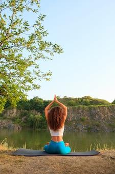 Mulher jovem praticando ioga perto do rio