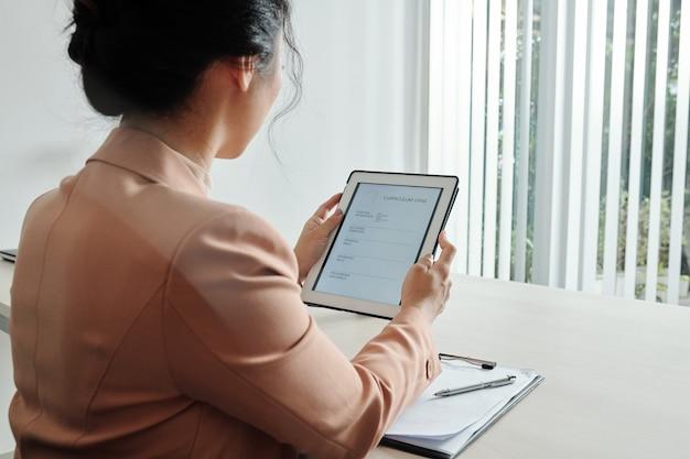 Mulher jovem preenchendo formulário cv em computador tablet, vista de trás