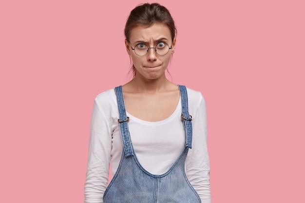 Mulher jovem preocupada aperta os lábios com uma expressão facial confusa, tenta descobrir uma saída, tem um olhar intrigado, usa óculos redondos grandes