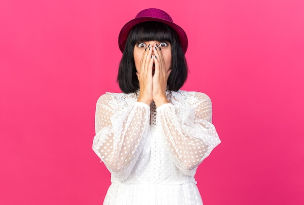 Mulher jovem preocupada com chapéu de festa, olhando para frente, mantendo as mãos na boca isoladas na parede rosa