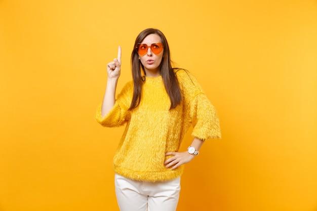 Mulher jovem preocupada com suéter, óculos coração laranja apontando o dedo indicador para cima no espaço da cópia isolado em fundo amarelo brilhante. emoções sinceras de pessoas, conceito de estilo de vida. área de publicidade.